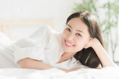 Young teenage girl lying in white bed room Royalty Free Stock Images