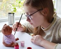 Young teenage girl makes toy, paints clay pig with gouache. Creative leisure for children. Supporting creativity, learning by royalty free stock photography