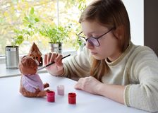 Young teenage girl makes toy, paints clay pig with gouache. Creative leisure for children. Supporting creativity, learning by royalty free stock image