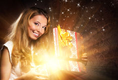 A young teenage girl opening a Christmas present. A young, happy and emotional teenage girl opening the magical Christmas present box. The image is taken on a royalty free stock photo