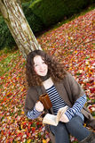 Young Teenage Girl outside reading a book during Autumn Season Stock Images