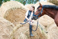 Young teenage girl owner sitting near her red horse. Pretty young teenage girl owner sitting on yellow hay/straw rolled stack near her favorite bay horse at farm stock photos