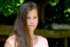 Young teenage girl in the park with calm facial expression. Stock Photos