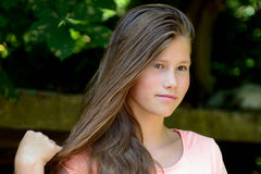 Young teenage girl in the park with calm facial expression. Royalty Free Stock Images
