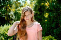 Young teenage girl in the park with calm facial expression. Young teenage girl in the park with long blond hair and relexed facial expression Stock Photo