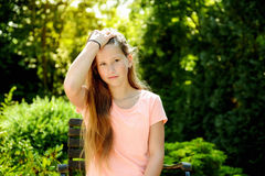 Young teenage girl in the park with calm facial expression. Young teenage girl in the park with long blond hair and relexed facial expression Royalty Free Stock Images