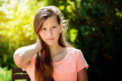 Young teenage girl in the park with calm facial expression. Young teenage girl in the park with long blond hair and relexed facial expression Stock Image