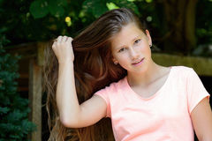 Young teenage girl in the park with long blond hair and facial expression. Royalty Free Stock Photography