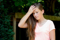 Young teenage girl in the park with thinking facial expression. Stock Photography