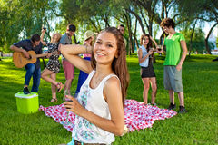 Young teenage girl partying with friends. Smiling and holding a glass of red wine as her college classmates picnic and play guitar in the background royalty free stock photo