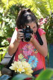 Young Teenage Girl Photographer. Taking pictures of flowers Stock Photos