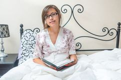 Young teenage girl reading in bed Royalty Free Stock Photos