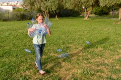 Kid cleaning in park.Volunteer teenager girl cleaning up litter. royalty free stock photo
