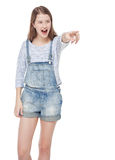Young teenage girl showing on something by finger and screaming. Isolated on white background Stock Photography