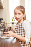 Young teenage girl sieving flour through the sieve Royalty Free Stock Photo