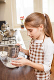Young teenage girl sieving flour through the sieve Stock Images