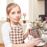 Young teenage girl sieving flour through the sieve Stock Photo