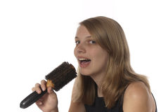 Young teenage girl singing into her hair brush. Stock Photo
