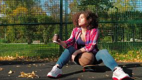 A young teenage girl sits on a skateboard on the playground, drinks coffee from a paper cup and holds a basketball ball. A young teenage girl with an african stock video footage