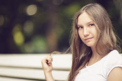 Young teenage girl sitting on bench Royalty Free Stock Images
