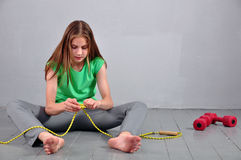 Young teenage girl sitting on the floor with skipping rope and dumbbells relaxing having rest in studio. Royalty Free Stock Photography