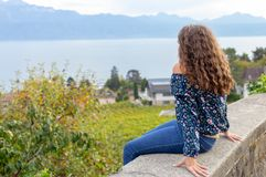 Girl. Teenage. Sitting. Outdoor. View. Young teenage girl sitting on the wall with beautiful Geneva lake on the background royalty free stock images