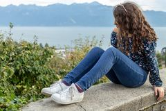 Girl. Teenage. Sitting. View. Outdoor scene. Young teenage girl sitting on the wall with beautiful Geneva lake on the background royalty free stock photo