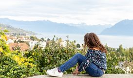 Girl. Teenage. View. Sitting. Outdoor. Young teenage girl sitting on the wall with beautiful Geneva lake on the background stock image