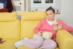 Young teenage girl sitting in a yellow sofa drinking orange juice. A young teenage girl sitting in a yellow sofa drinking orange juice stock image
