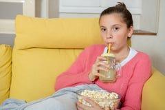 Young teenage girl sitting in a yellow sofa drinking orange juice. A young teenage girl sitting in a yellow sofa drinking orange juice stock images