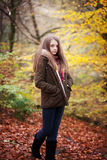 Young teenage girl standing in a forest in Autumn royalty free stock image