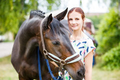 Young teenage girl standing with her bay mare Stock Photo