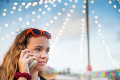 A young teenage girl talks on her mobile phone at an open-air flea market royalty free stock images