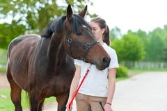 Young teenage girl tenderly kissing her favorite chestnut horse Stock Image