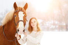 Young teenage happy girl with horse in winter park Stock Images
