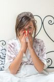 Young teenage sick girl sitting in bed Stock Photo
