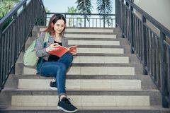 A young teenage student in university. Smiling and reading the book in summer holiday. She listening the music while reading the book Stock Photo
