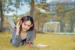 A young teenage student in university. Smiling and reading the book in summer holiday. She listening the music while reading the book Stock Images