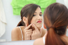 Young teenage woman with pimple Royalty Free Stock Photos