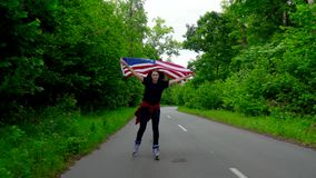 Young teenage woman with US flag is roller skating through woods and holds the hand of another person. The concept of Independence Day USA stock video footage