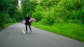 Young teenage woman with US flag is roller skating through woods and holds the hand of another person. The concept of Independence Day USA stock footage