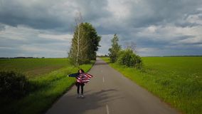 Young teenage woman waving a US flag is roller skating on the rural road. The concept of Independence Day USA stock video