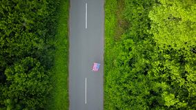 Young teenage woman waving a US flag is roller skating on the rural road. View from the top stock video