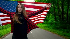 Young teenage woman waving a US flag is roller skating through woods. Slow motion stock video