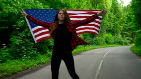 Young teenage woman waving a US flag is roller skating through woods. Slow motion stock footage