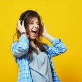 Young teenage woman wearing headphones screams Stock Images