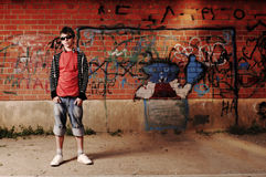 Young Teenager against Graffiti Wall. Young Teenager with sunglasses and headphones against Graffiti Wall Stock Images
