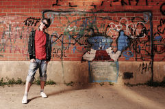 Young Teenager against Graffiti Wall. Young Teenager with sunglasses and headphones against Graffiti Wall Royalty Free Stock Images