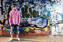 Young Teenager against graffiti wall. Young Teenager in sunglasses wearing a striped shirt and jean shorts against Graffiti Wall.No recognizable inscriptions on Royalty Free Stock Images