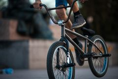 Young teenager bicyclist boy riding on beautiful orange bmx bicycle male hobby extreme sport male hobby lower part closeup backgro. Young teenager bicyclist boy royalty free stock photography